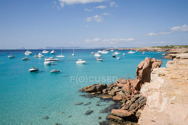 Yachts and ships moored in azure water under blue cloudy sky — Stock Photo