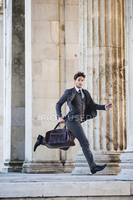Вид сбоку середины взрослого мужчины носить полный костюм, перевозящих чехол, работает, в середине воздуха, глядя на камеру — стоковое фото
