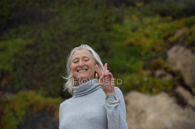 Mature woman making victory sign — Stock Photo