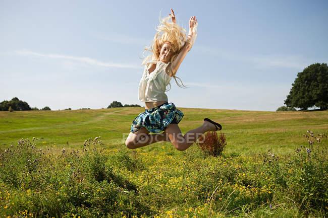 Молодая женщина в поле, прыгать в воздухе — стоковое фото