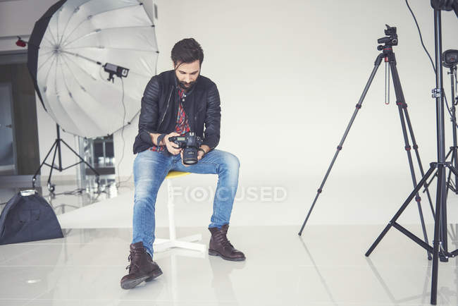 Male photographer reviewing studio photo shoot on digital slr — Stock Photo