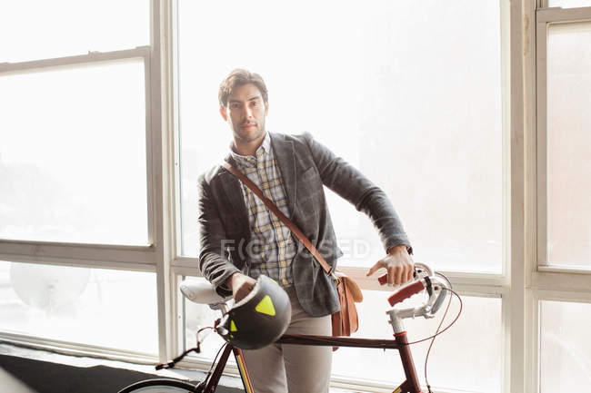 Man standing with bicycle by window — Stock Photo