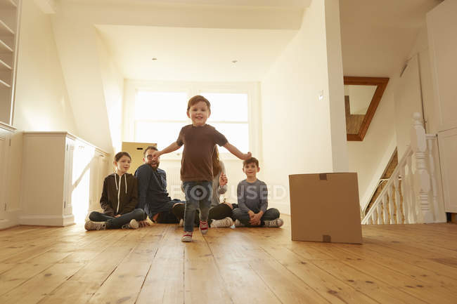 Portrait of male toddler and family sitting on floor in new home — Stock Photo