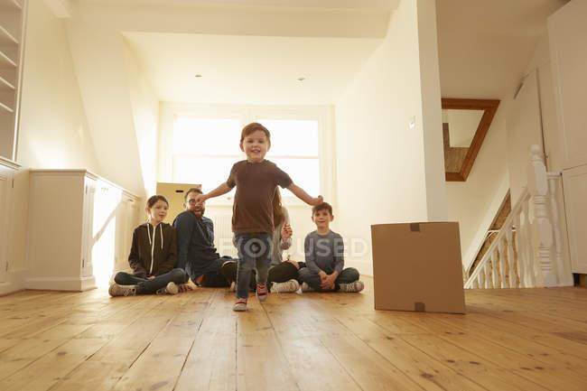 Ritratto di bambino e famiglia seduti sul pavimento in una nuova casa — Foto stock