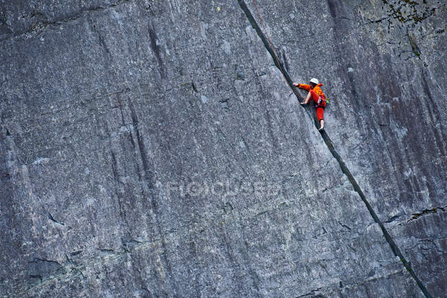 Climber scaling steep rock face — Stock Photo