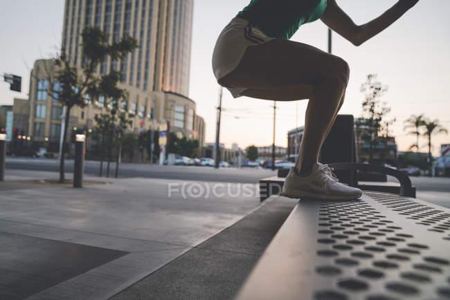 Молода жінка, що здійснюють на відкритому повітрі, активізується на лавці — стокове фото