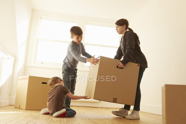 Niña y dos hermanos levantando caja de cartón en un nuevo hogar - foto de stock