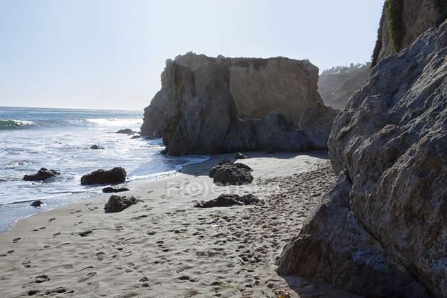 Небольшой песчаный пляж, на скалистом побережье — стоковое фото