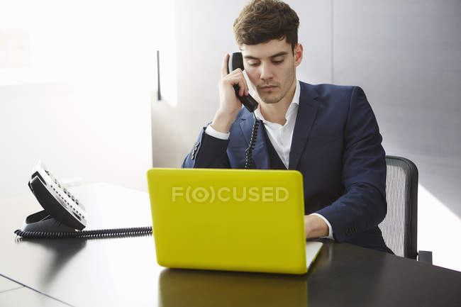 Man sitting at desk using laptop making telephone call — Stock Photo