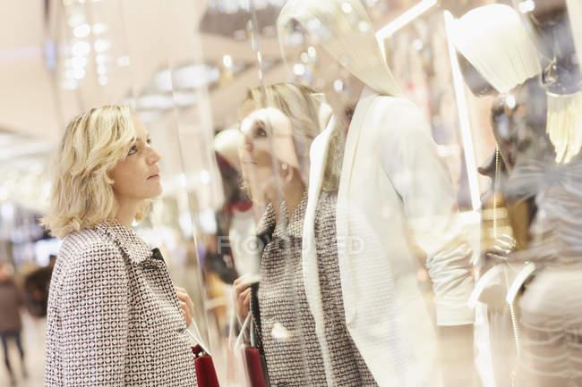 Metà adulto shopper femminile guardando vetrina nel centro commerciale — Foto stock