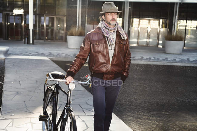 Mid adult man walking with bicycle in city — Stock Photo