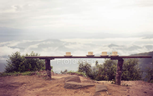 Cups and saucers on a bench — Stock Photo
