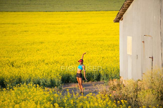 Молода жінка бігун розтягування в галузі ріпак — стокове фото