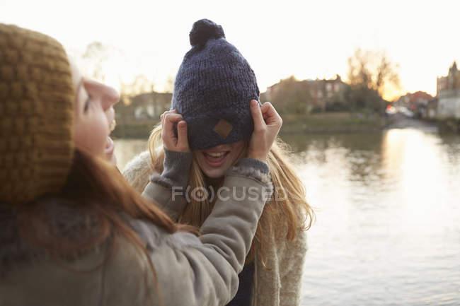 Junge Frau setzt Freundin Strickmütze auf — Stockfoto