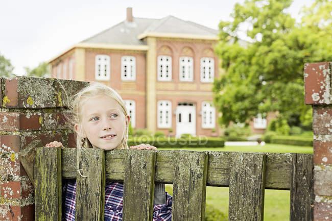 Девушка у деревянных ворот, отворачиваясь — стоковое фото