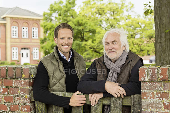 Father and son leaning on wooden gate — Stock Photo