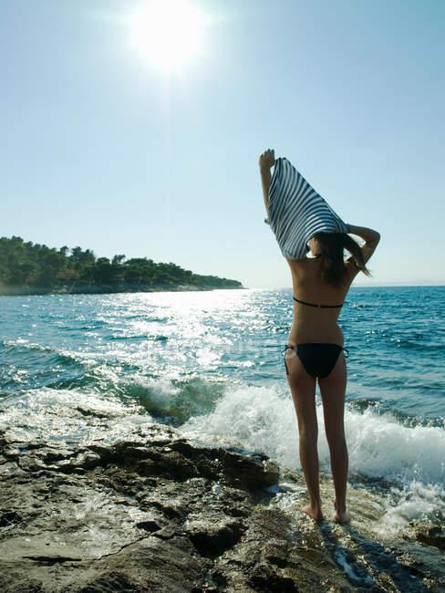 Молодая женщина снимает футболку у моря — стоковое фото