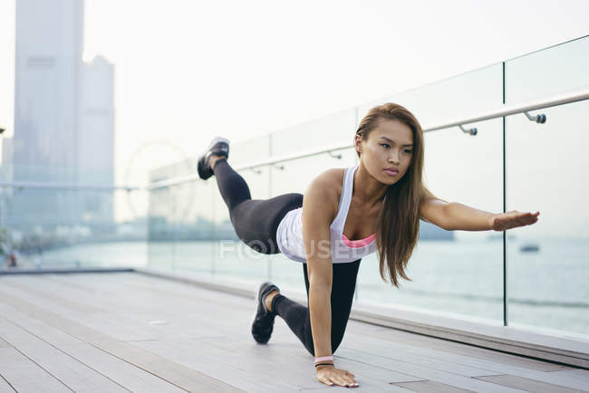 Junge Frau dabei kniend Dehnübungen am Wasser, Hong Kong — Stockfoto