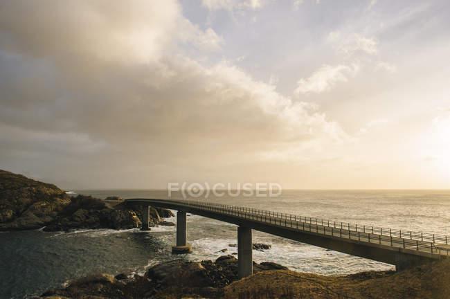 Ponte sagomato sulla costa contro il cielo nuvoloso, Reine, Lofoten, Norvegia — Foto stock