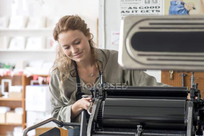 Imprimante femelle préparant la machine d'impression en atelier — Photo de stock