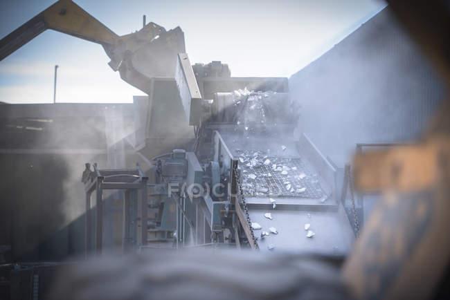 Machinery crushing titanium metal in industrial plant — Stock Photo
