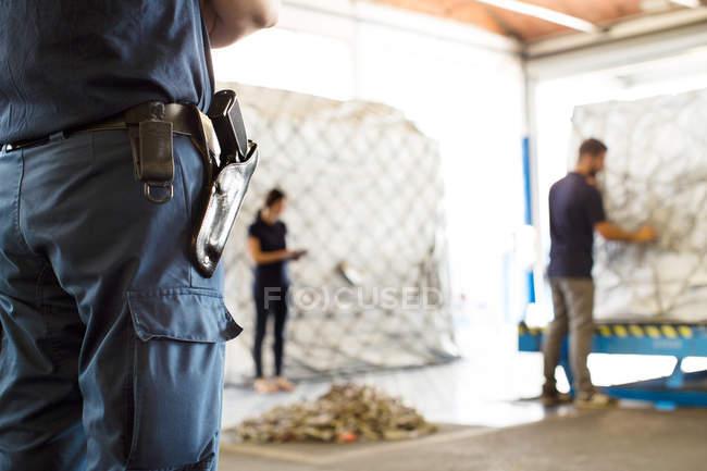 Guardia de seguridad vigilando trabajadores en almacén de carga aérea - foto de stock