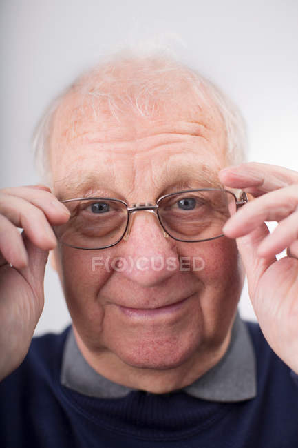 Porträt von senior woman Anpassung der Gläser, Studio gedreht — Stockfoto