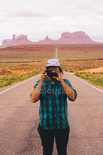 Молодой человек фотографирует с дороги, Долина Монументов, Аризона, США — стоковое фото