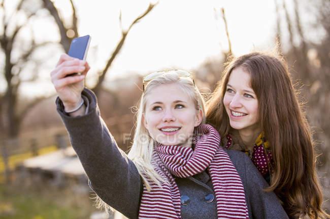 Девочки-подростки делают селфи со смартфоном — стоковое фото