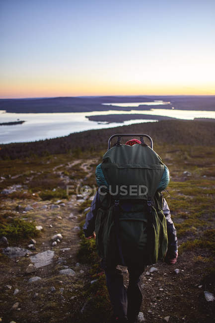 Back view of hiker walking with backpack near lake in keimiotunturi, finland — Stock Photo
