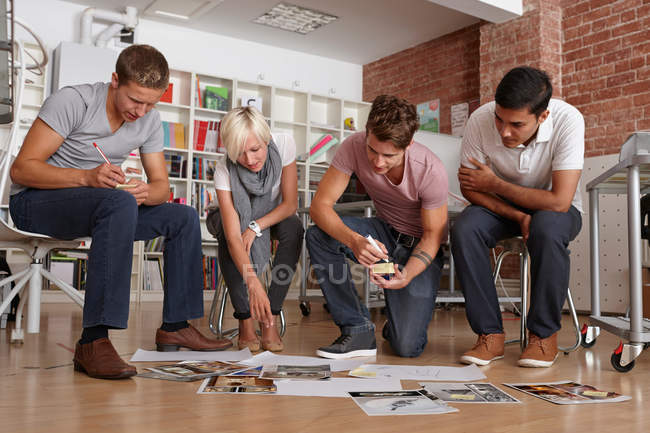 Colleagues looking at papers on floor in meeting room — Stock Photo