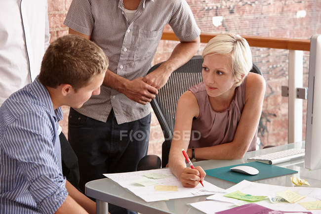 Four colleagues designers discussing in meeting room — Stock Photo