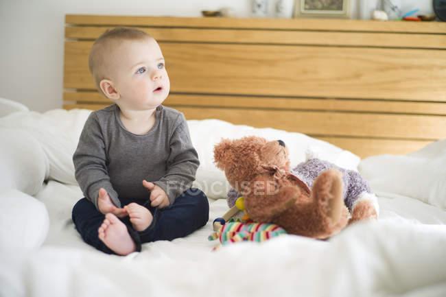 Chéri s'asseyant sur le lit avec l'ours de nounours regardant loin — Photo de stock