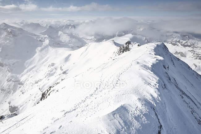 Catena montuosa innevata con nuvole nebbiose — Foto stock