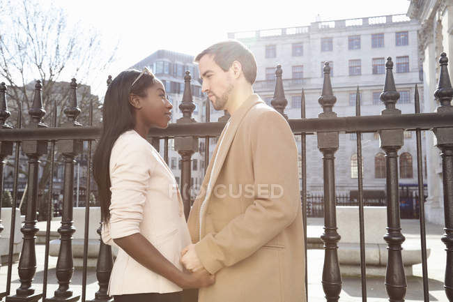 Couple standing in street, face to face, holding hands — Stock Photo
