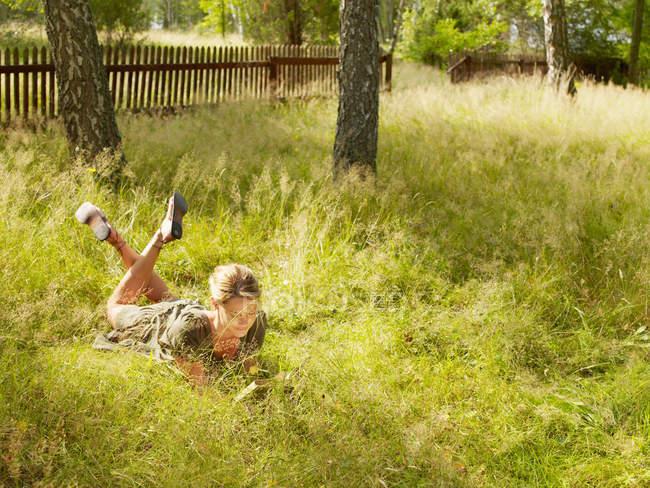 Женщина лежит в траве и читает — стоковое фото