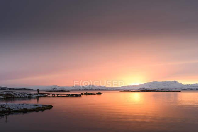 Силует стоїть на пристані на озеро на заході сонця — стокове фото