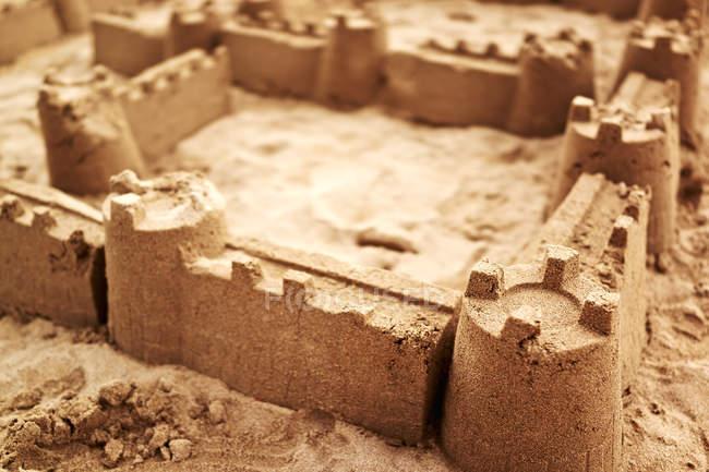 Песчаный замок, построенный из песчаного морского берега, крупным планом — стоковое фото