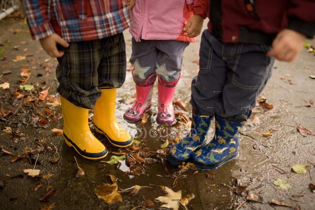 Three children wearing wellington boots — Stock Photo