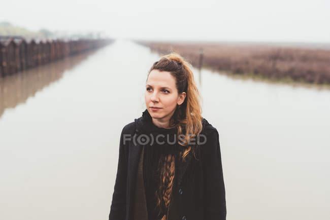 Porträt einer jungen Frau am nebligen Ufer des Kanals — Stockfoto