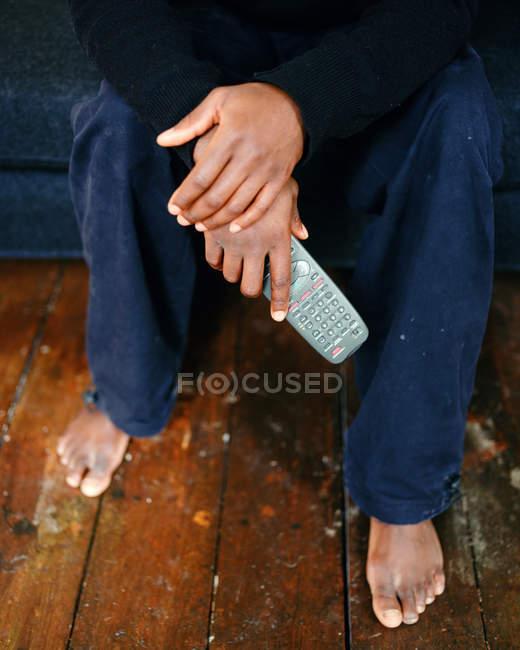 Immagine ritagliata dell'uomo con un telecomando in mano — Foto stock