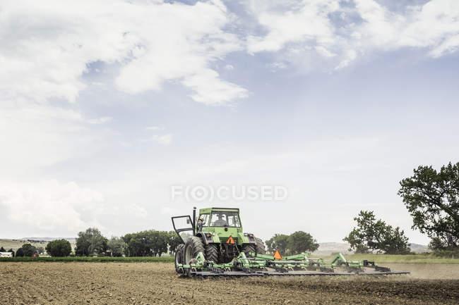 Agriculteur et petit-fils adolescent agitant tout en labourant avec tracteur — Photo de stock