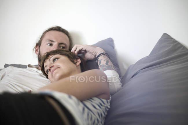 Pareja en el abrazo amoroso en la cama - foto de stock