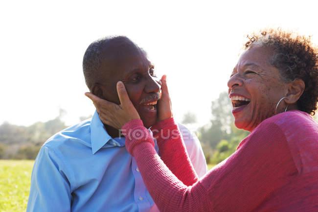 Портрет старшого пара в парку, жінка, торкаючись обличчя людини — стокове фото