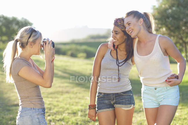 Three young female friends posing for photographs — Stock Photo