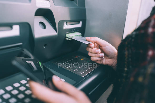 Female hand inserting credit card into cash machine — Stock Photo