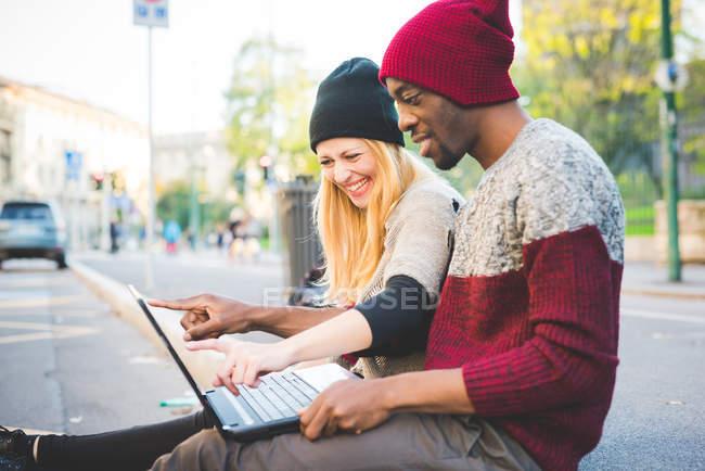 Casal usando laptop no pavimento ao ar livre durante o dia — Fotografia de Stock