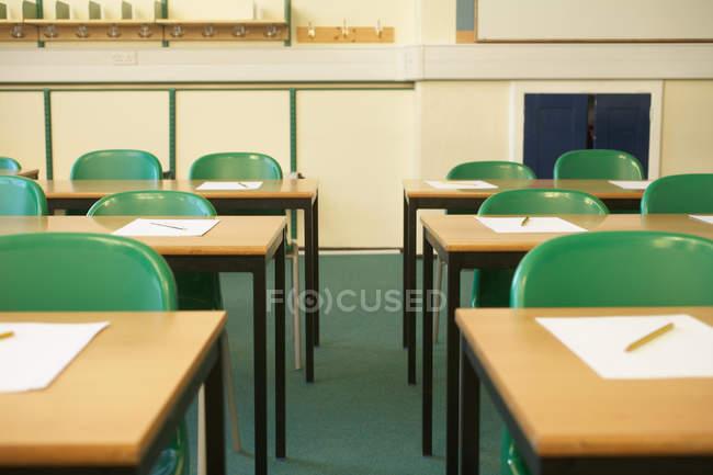 Leere Schreibtische mit Papieren im Klassenzimmer — Stockfoto
