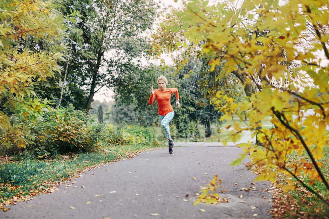 Corredor feminino jovem correndo ao longo do caminho do parque — Fotografia de Stock
