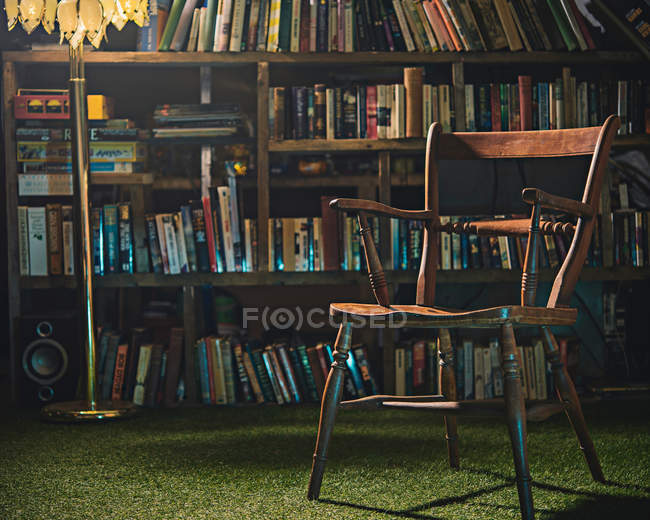 Chair and lamp in front of bookcase — Stock Photo